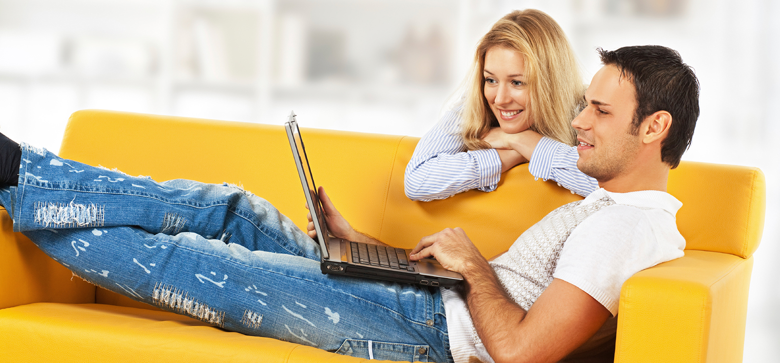 Man sitting on couch looking at laptop.  Woman looking over his shoulder.